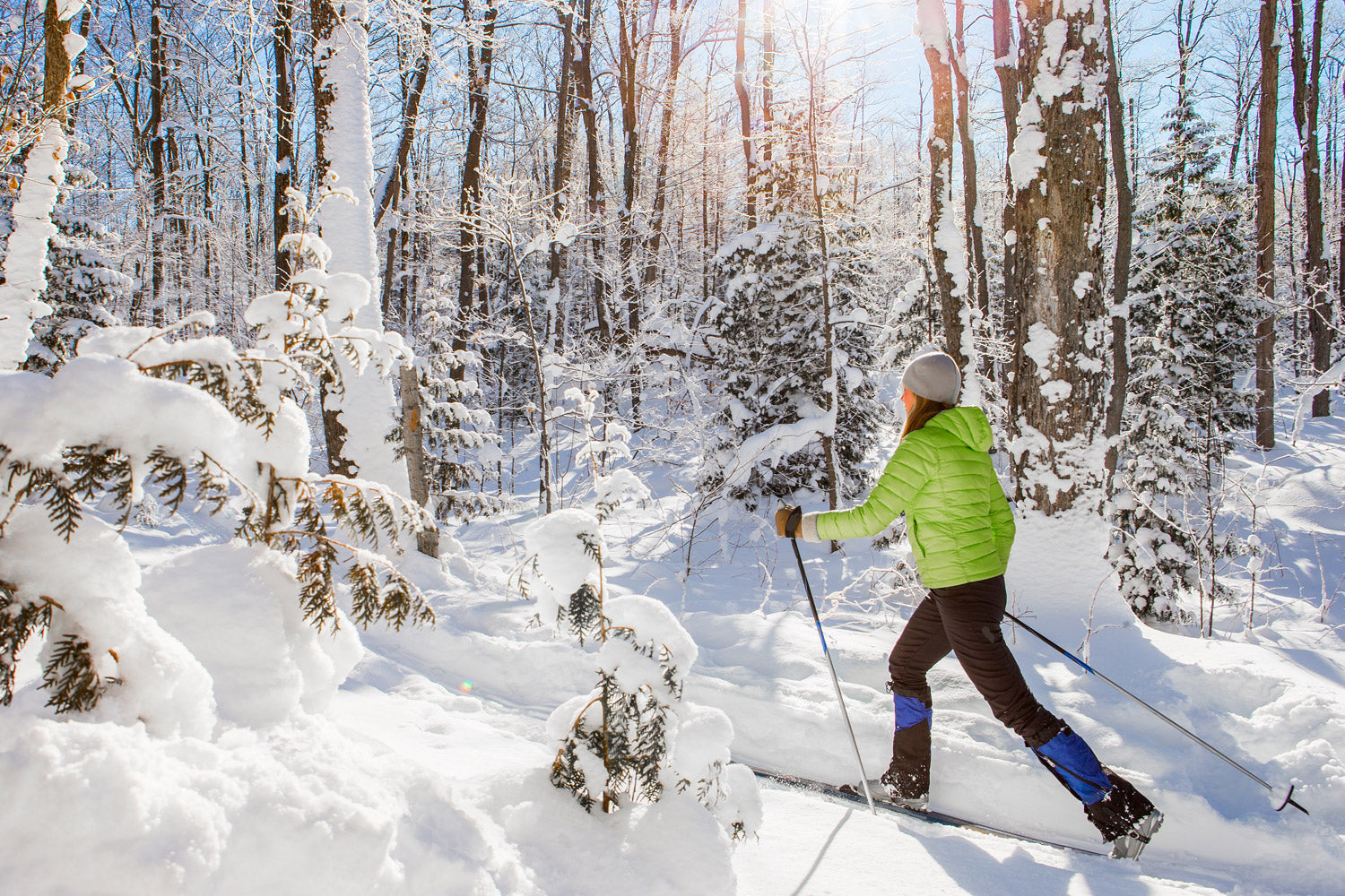 Young woman skiing through a snow covered forest on nordic skis