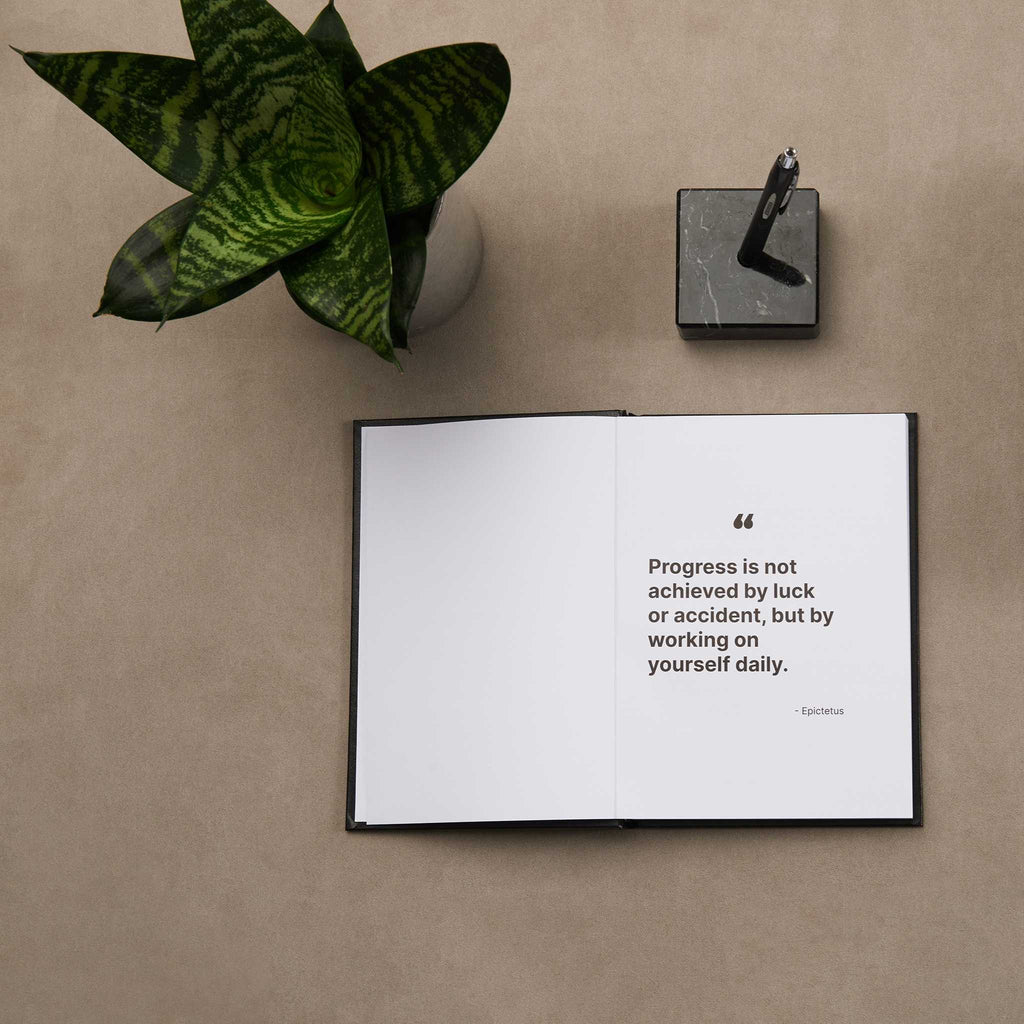 Hardcover A5 journal lay flat open showing inspirational quote with black pen and green plant