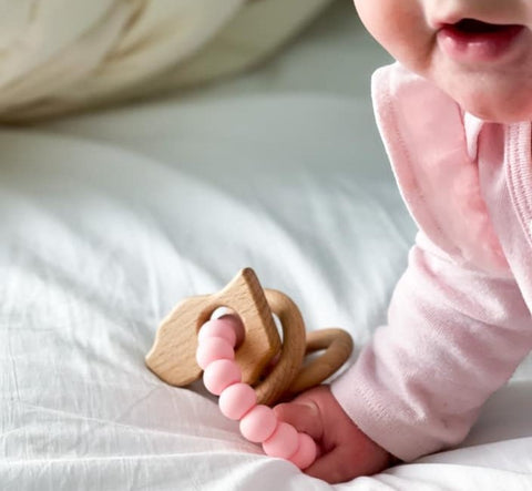 Baby holding natural silicone teether rattle - MAE + Me Teething Co