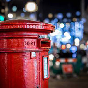 Red post box mail box letter box on Oxford Street in London at night at Christmas