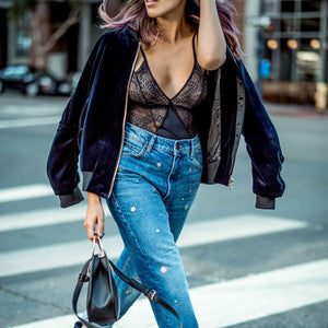 Woman crossing the road wearing a black lace body under a black bomber jacket coat and blue jeans carrying a black handbag