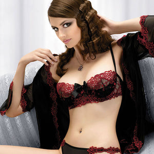 Brunette model sat on a sofa touching her hair wearing a black and red bra thong and peignoir set