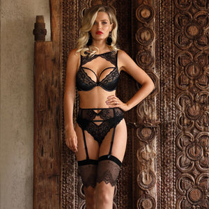 Pretty blonde model standing with her hand on her hip wearing a black bra with neck feature black stockings and suspenders and black briefs