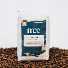 Load image into Gallery viewer, A white bag of coffee sitting on a shallow pile of whole bean coffee. The label reads: MDC, The Duet, Whole Bean Coffee, Rich, Comforting, & Full-bodied. Net wt. 12 oz (340g).
