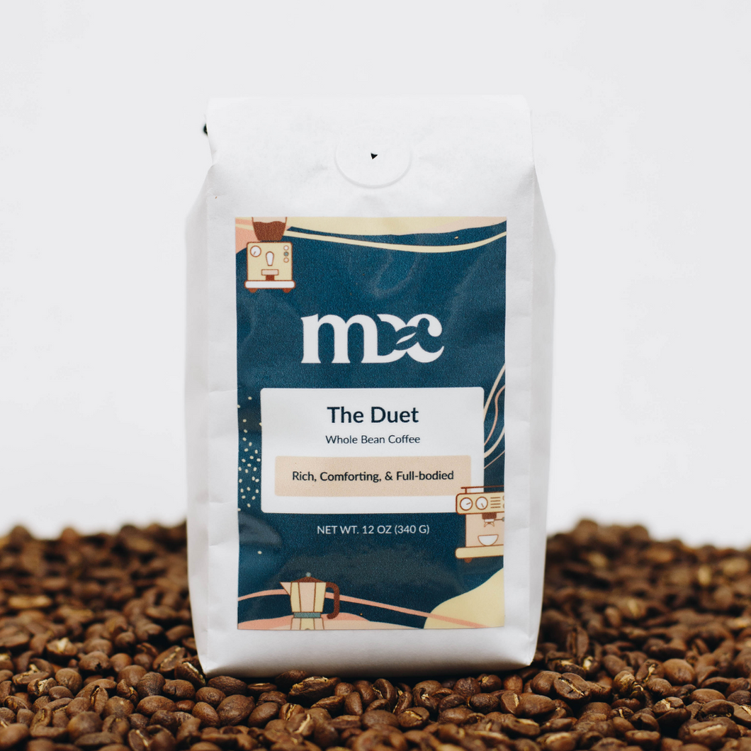 A white bag of coffee sitting on a shallow pile of whole bean coffee. The label reads: MDC, The Duet, Whole Bean Coffee, Rich, Comforting, & Full-bodied. Net wt. 12 oz (340g).