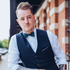 man with vest and dark green bow tie