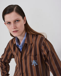 Model wears The Academy New York Crest PJ shirt in brown/blue.