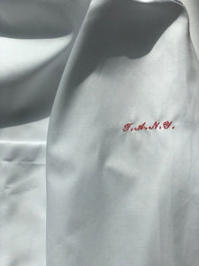 "The Academy New York. Classic Oxford blue button-down shirt in white, featuring ""T.A.N.Y."" embroidered on the left shoulder. (detail)"