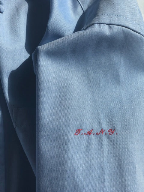 "The Academy New York. Classic Oxford blue button-down shirt in blue, featuring ""T.A.N.Y."" embroidered on the left shoulder. (detail)"