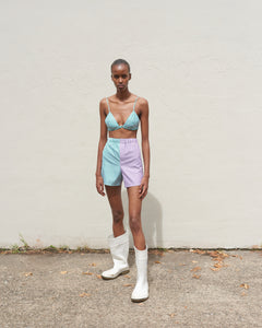 Model wears The Academy New York off court green and purple striped boxer shorts and bra top.