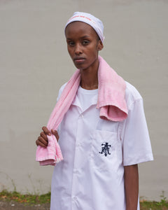 Model wears The Academy New York Club shirt in pink with a pink towel around her neck.