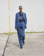 "Load image into Gallery viewer, Model wears The Academy New York SS21 Club Jacket and Double Pleat Pant in Overdyed Lilac.  She wears the black ""Apres Tenez"" t shirt underneath."