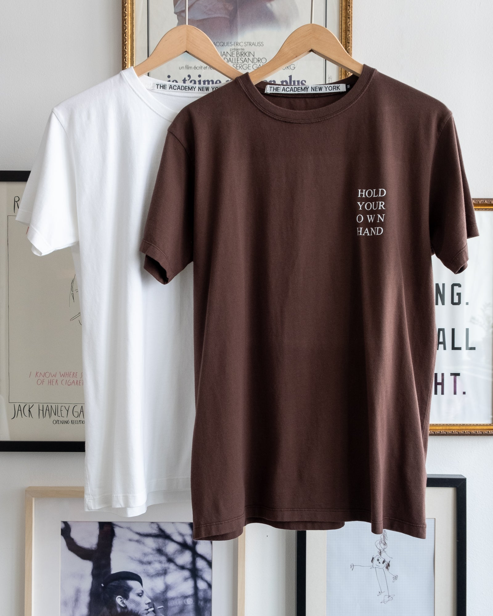 "The Academy New York white and turkish coffee t shirts with ""hold your own hand"" printed."