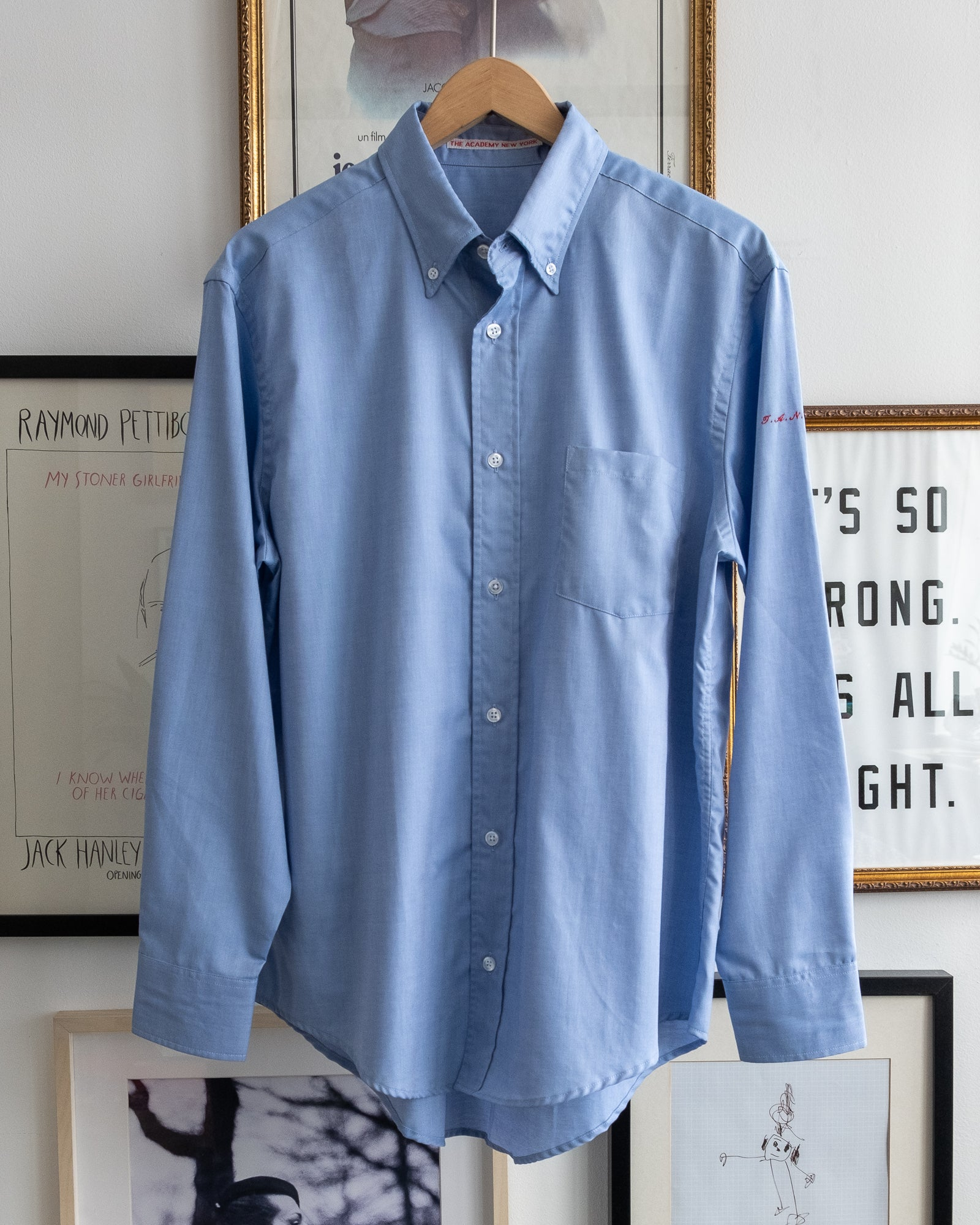 "The Academy New York. Classic Oxford blue button-down shirt in blue, featuring ""T.A.N.Y."" embroidered on the left shoulder. (front)"
