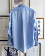"Load image into Gallery viewer, The Academy New York. Classic Oxford blue button-down shirt in blue, featuring ""T.A.N.Y."" embroidered on the left shoulder. (back)"
