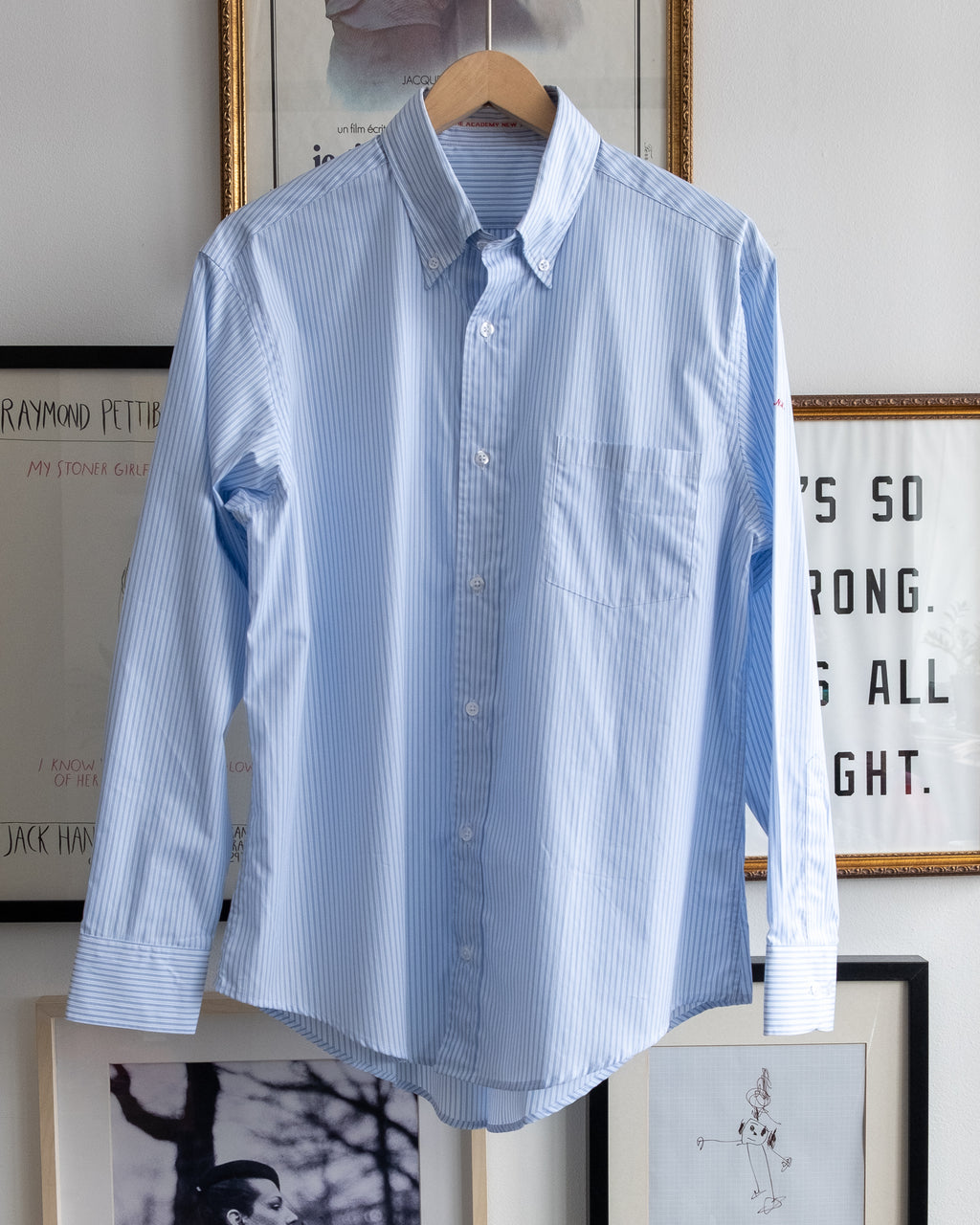 "The Academy New York. Classic Oxford blue button-down shirt in blue and white stripe, featuring ""T.A.N.Y."" embroidered on the left shoulder. (front)"