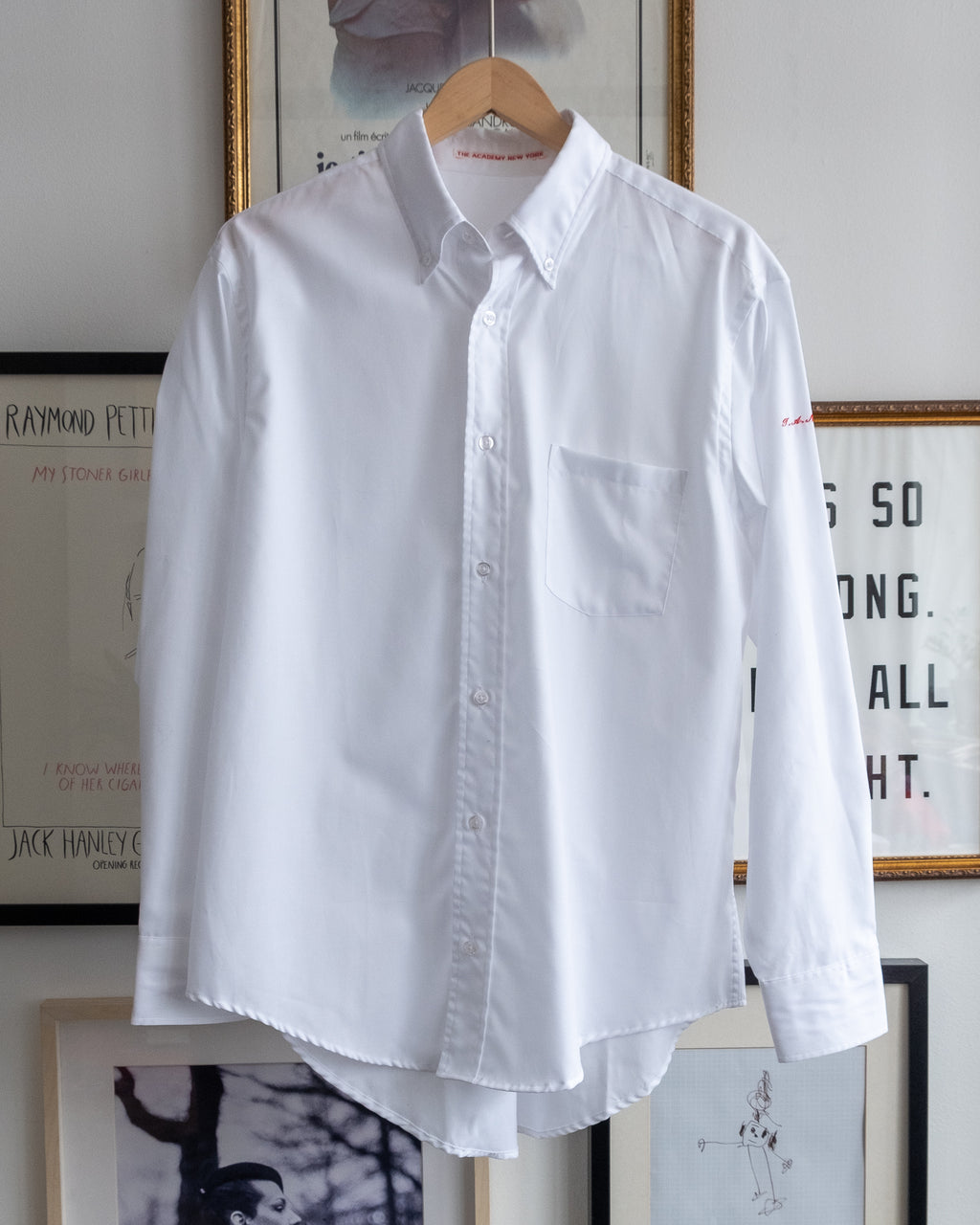 "The Academy New York. Classic Oxford blue button-down shirt in white, featuring ""T.A.N.Y."" embroidered on the left shoulder. (front)"