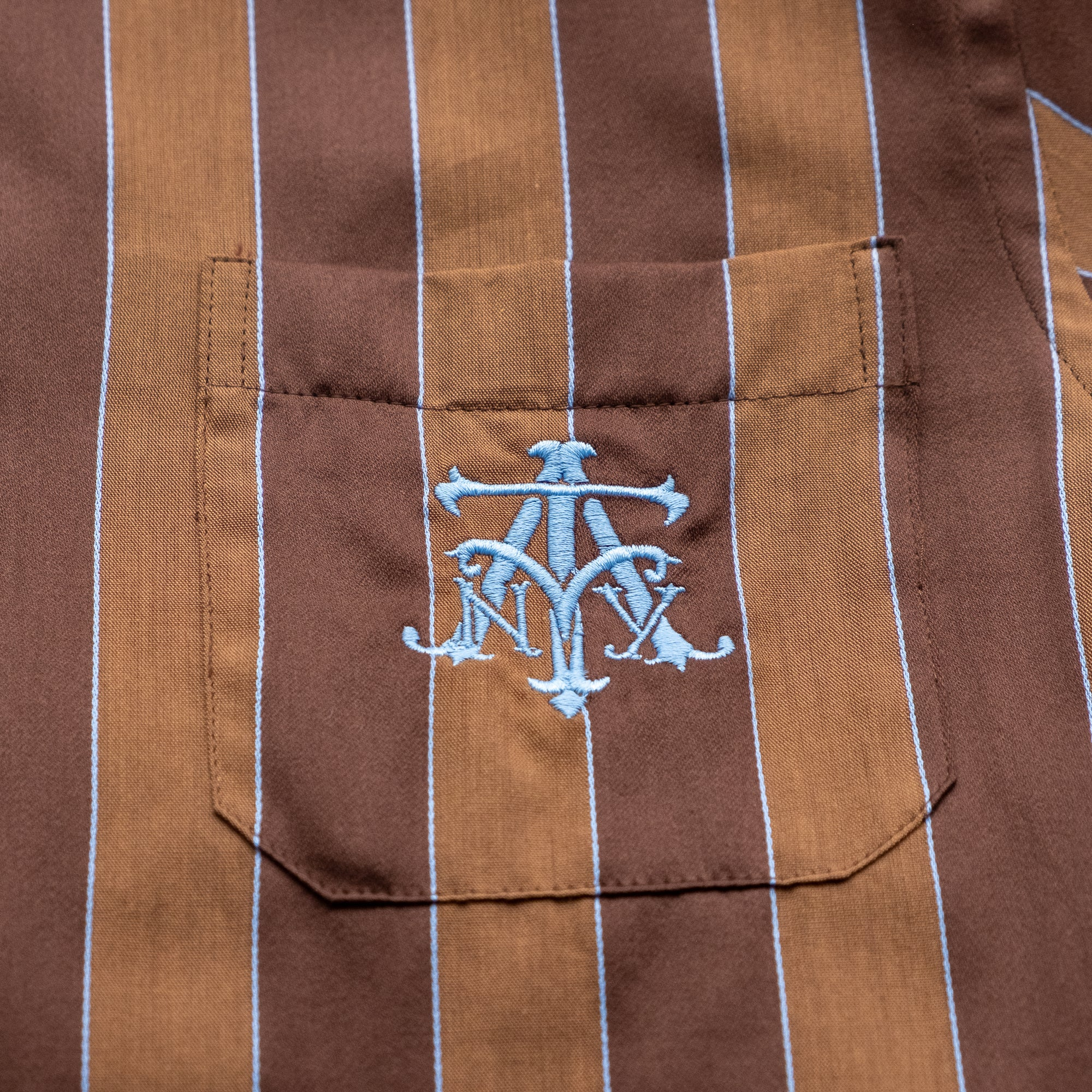 The Academy New York Crest PJ shirt in brown/blue close up of blue embroidered crest.