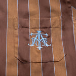 Load image into Gallery viewer, The Academy New York Crest PJ shirt in brown/blue close up of blue embroidered crest.