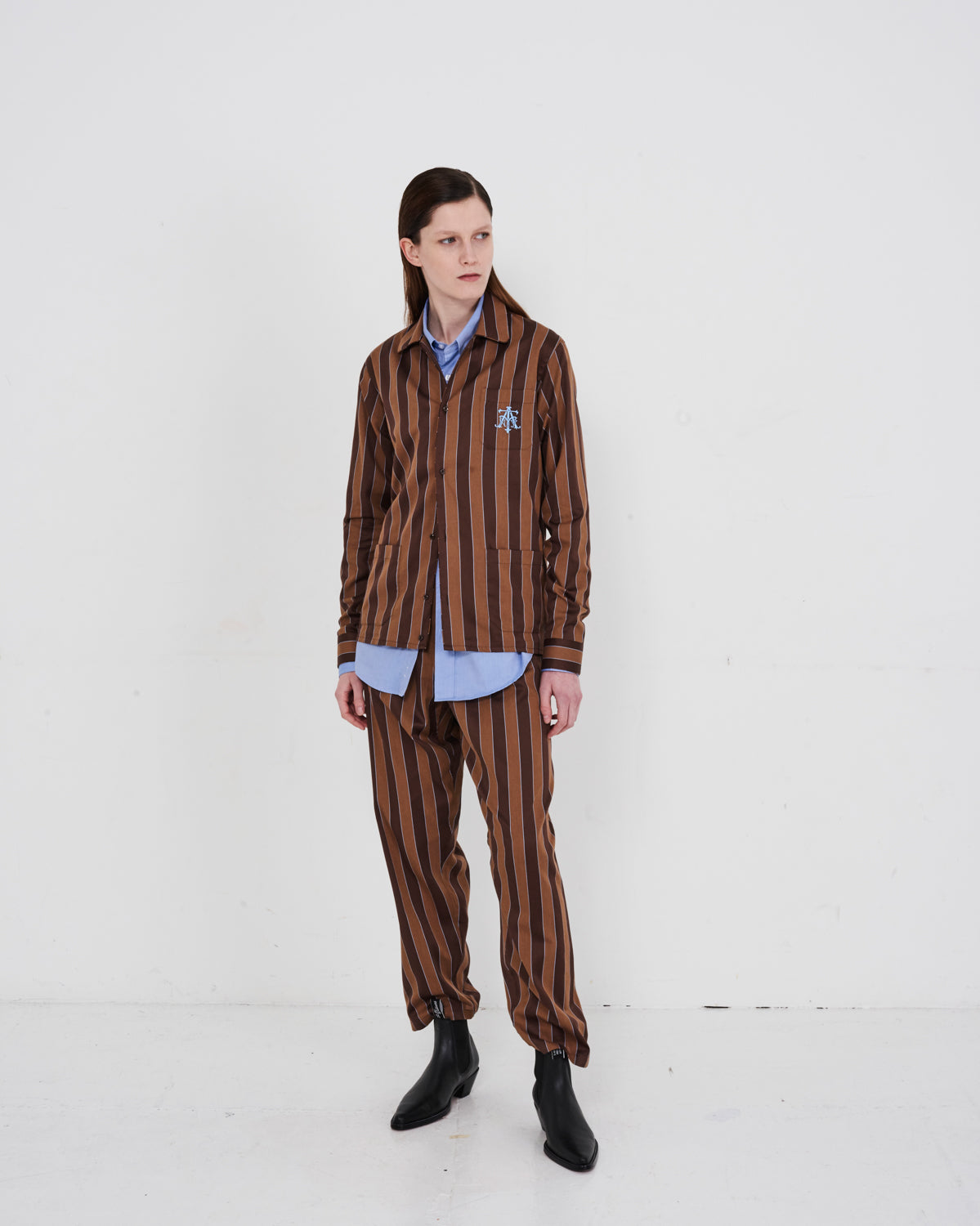 Model wears The Academy New York Crest PJ Shirt and PJ Pant in brown/blue stripe.
