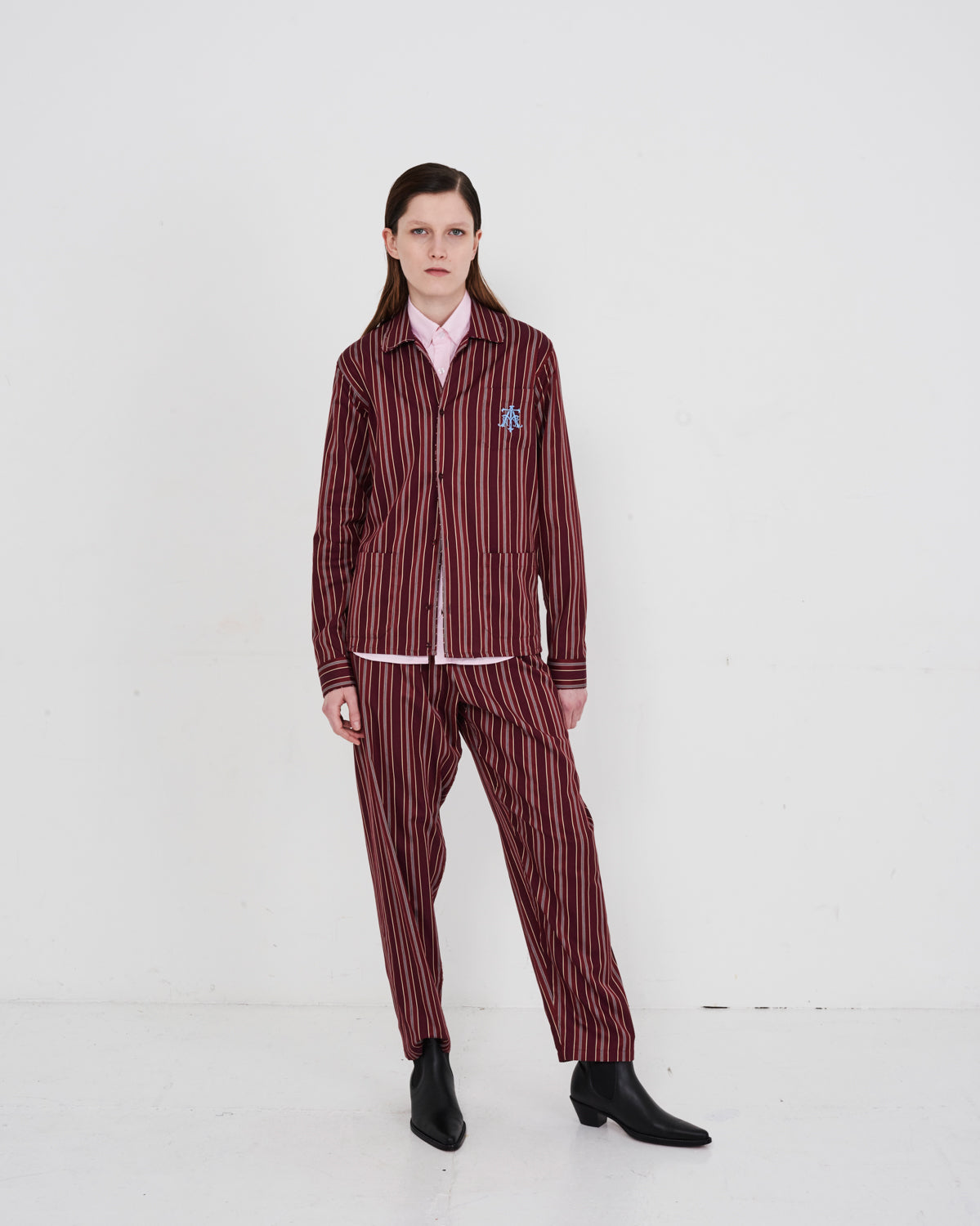 Model wears The Academy New York Crest PJ Shirt and PJ Pant in burgundy stripe.