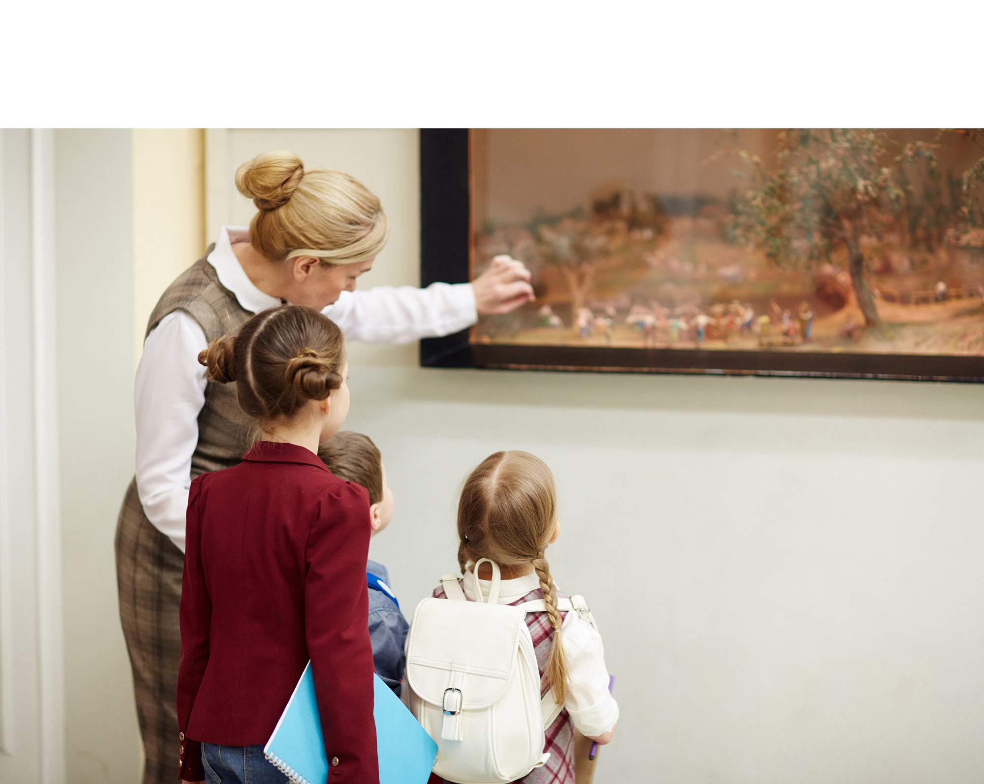Teacher pointing to a painting with two children looking on