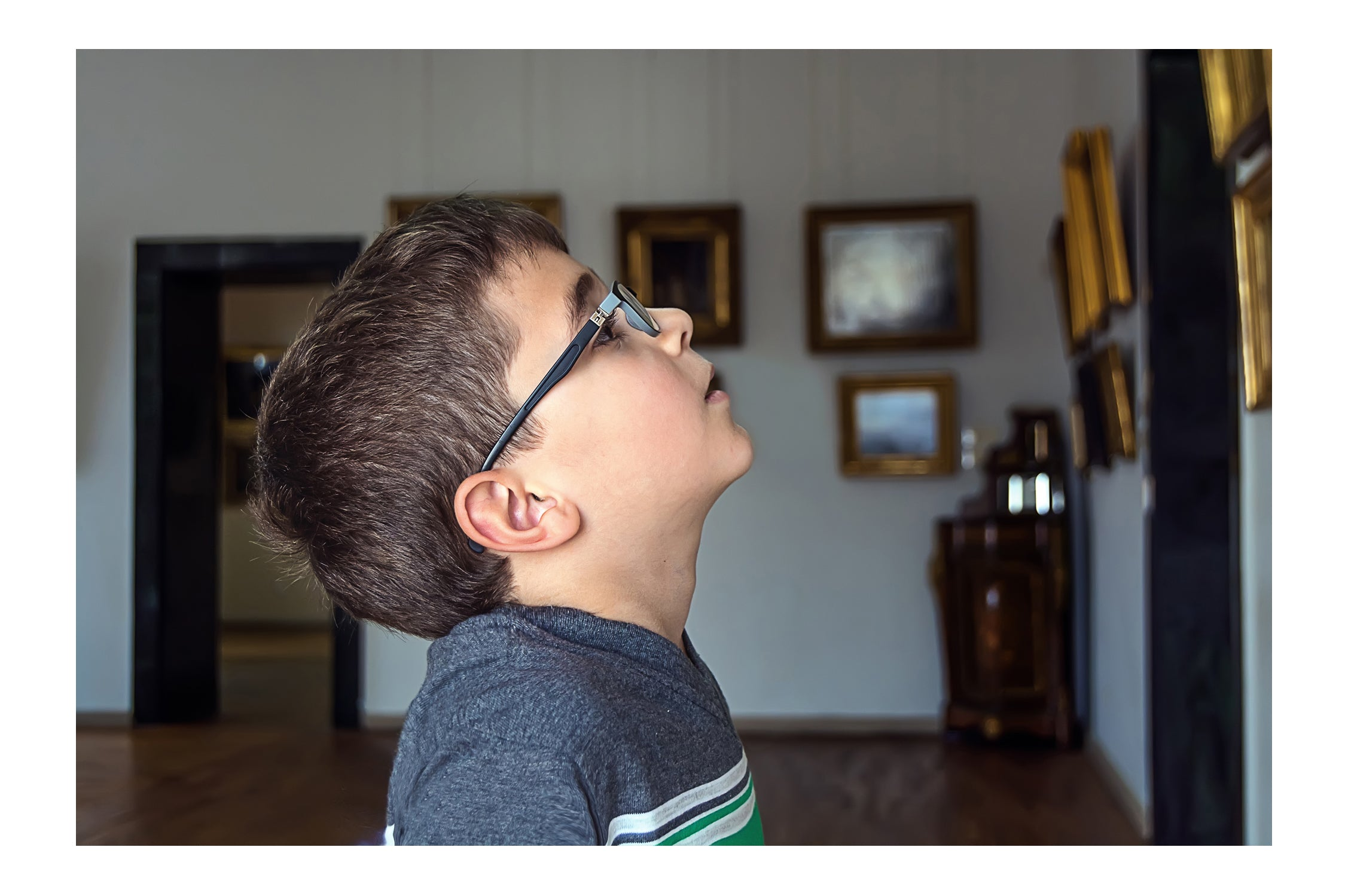 Boy looking at artwork with a curious expression on his face