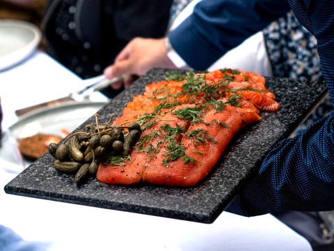 A whole fillet of gin cured salmon is on a black marble chopping board. It has chopped dill on top and a pile of caper berries and cornichons on one corner. A man serves some slices to a dinner guest using small silver tongs.