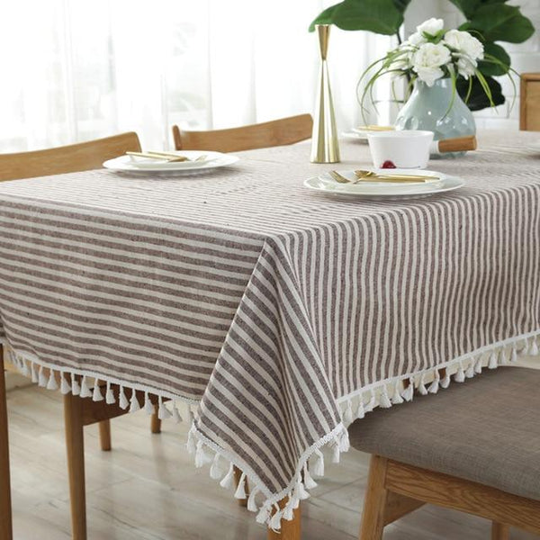 Image shows a striped table cloth with white tassels. The stripes are coffee and white colours. The table cloth is on a wood table wit chairs around it and a vase with green and white flowers