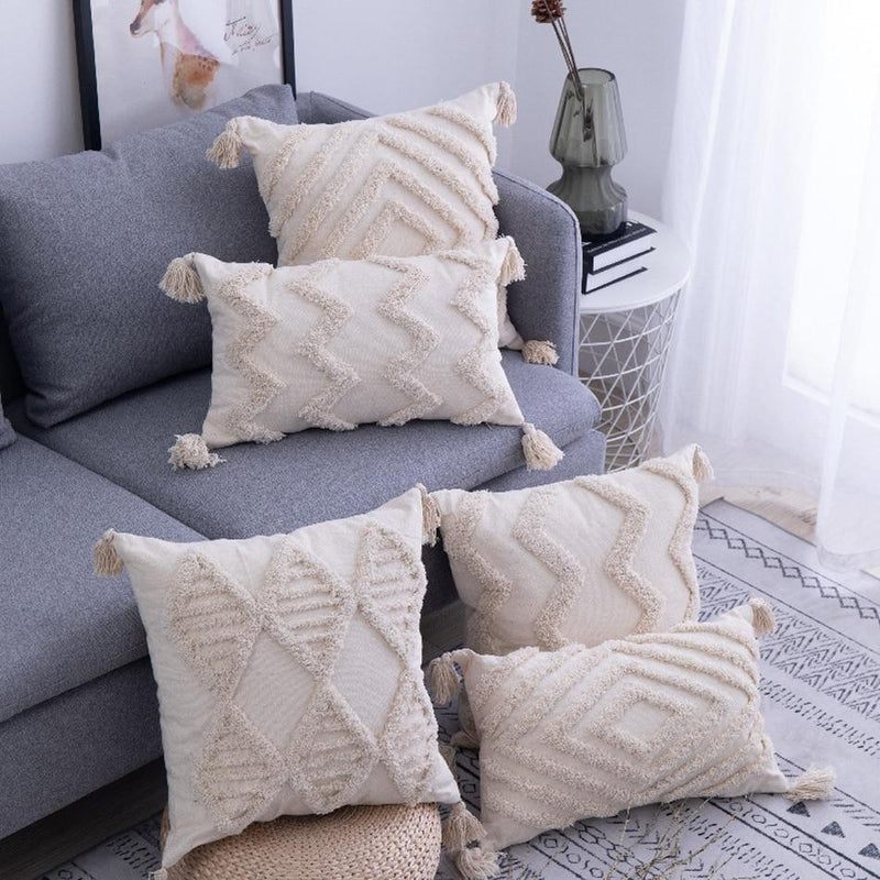 Image shows a group of cushions stacked around a grey sofa and on the floor. They are all an unbleached cotton colour with tassels on each corner and patterns in a heavy texture.