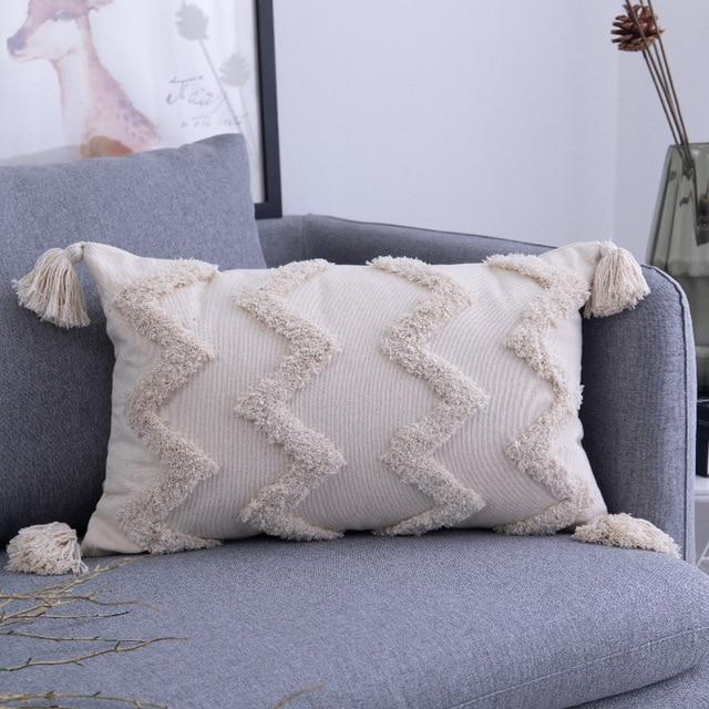Image shows an oblong cushion. It is an unbleached cotton colour with tassels on each corner and thick tuffed zigzag patterns