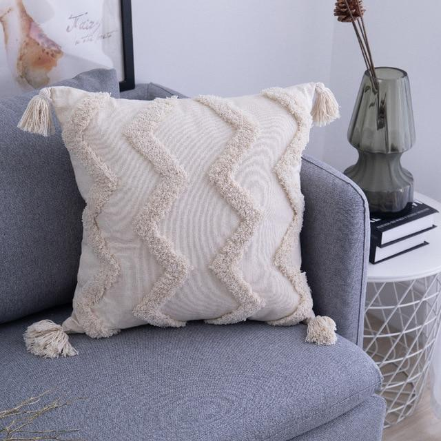 A square cushion with tassels on each of the four corners and a heavy textured ziz zag pattern. THe whole cushion is a natural unbleached cotton colour
