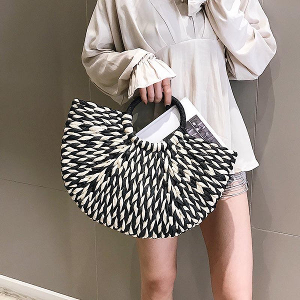 Image shows a women standing against a wall holding the black and white half moon bay bag. The handles a round and covered in black straw. The bag has a half moon shape and is woven black and white straw.