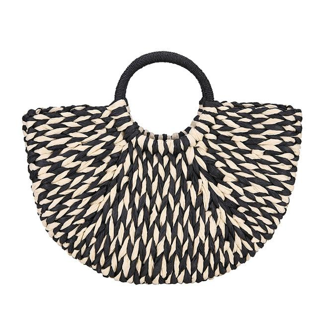 Image shows the black and white half moon bay bag. The handles are round circles and covered in black straw. The bag is  a half moon shape and is woven from black and white straw.