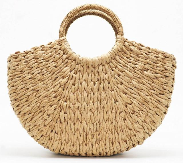 Image shows the half moon bay bag in sand. The bag is a half moon shape and is woven in a sand coloured straw. The handles are round and wrapped in sand coloured string.
