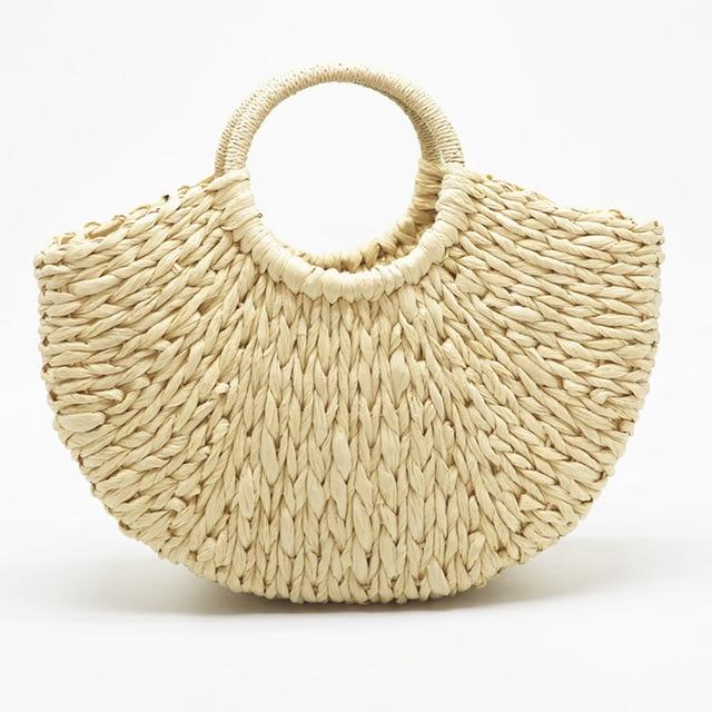 Image shows the half moon bay bag in toe toe. The bag is a half moon shape and is woven in a light cream coloured straw. The handles are round and covered in string the same colour as the bag.