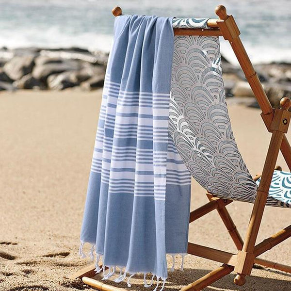 Image shows a beach towel over the back of a beach chair with sand and water in the distance. The towel is a thin turkish style and mostly grey with some white stripes.