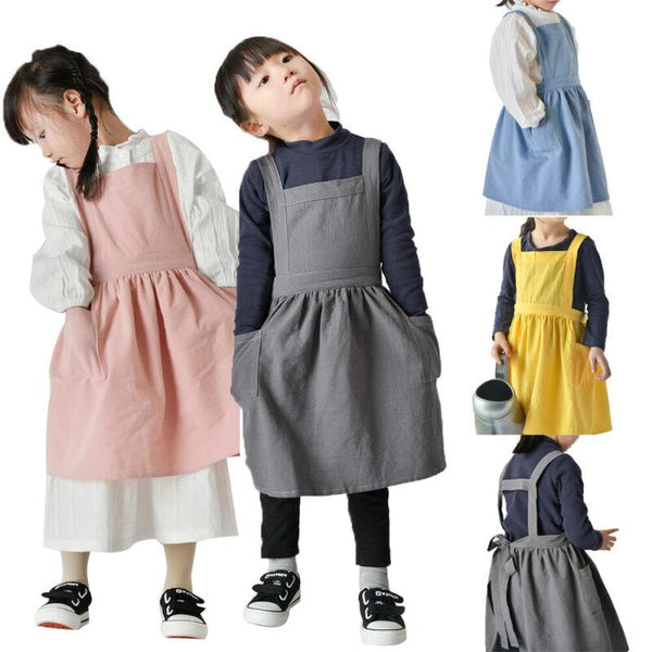 Image is a group shot showing children wearing each of the colours of this apron, grey, pink, blue and yellow. The aprons have two pockets, gather at the waist a bit and have a bib front with straps over the shoulders.