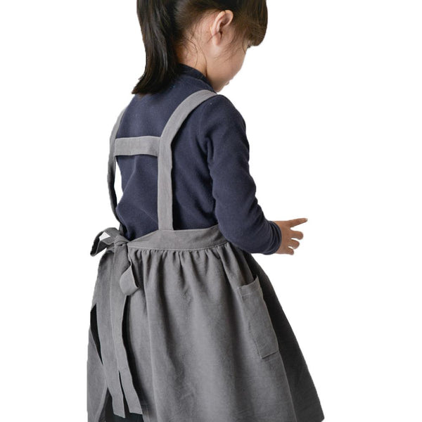 Image shows the reverse of the apron with shoulder straps, one horizontal strap between the should straps and a tie at back of the waist. One pocket is visible.