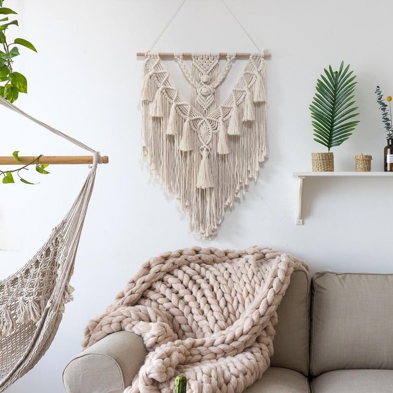 Image shows muriwai wall hanging on a white wall above a sofa. The room also has a shelf with post and plants and a hanging macrame chair copped on the edge of the photo.. The hanging is made from macrame weaving in the shape of a triangle with wood along the top. It is heavily textured weaving with tassles and geometric patterns. It is an unbleached cotton colour.