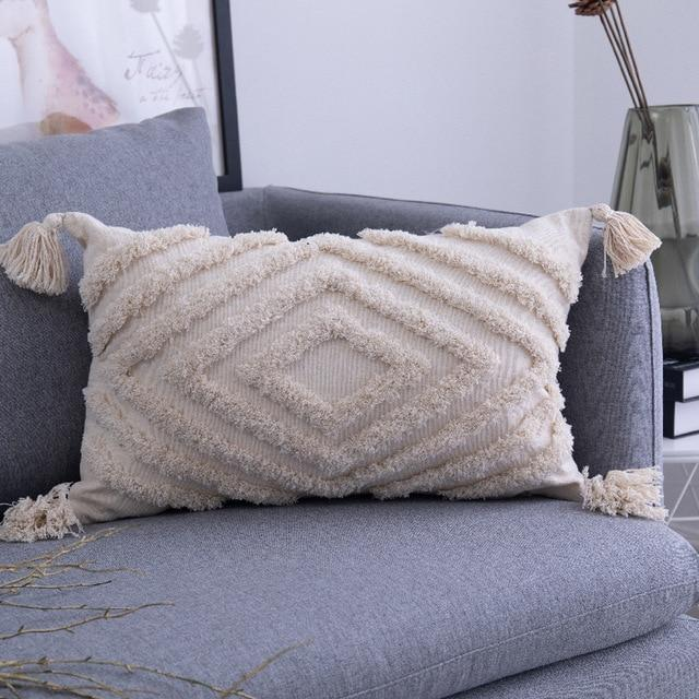 Image shows omaha cushion cover which is an oblong shape cover in an unbleached cotton colour. It has a tassel on each corner and deep textured tufting in the shape of diamonds.