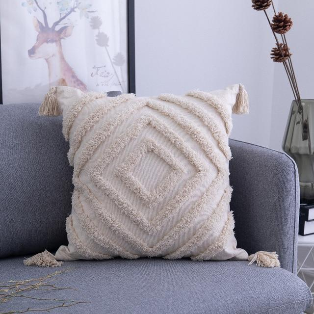 Image shows a square cushion on a grey sofa. The cushion is an unbleached cotton colour. It has a tassel on each corner and is heavily textured with diamond patterns.