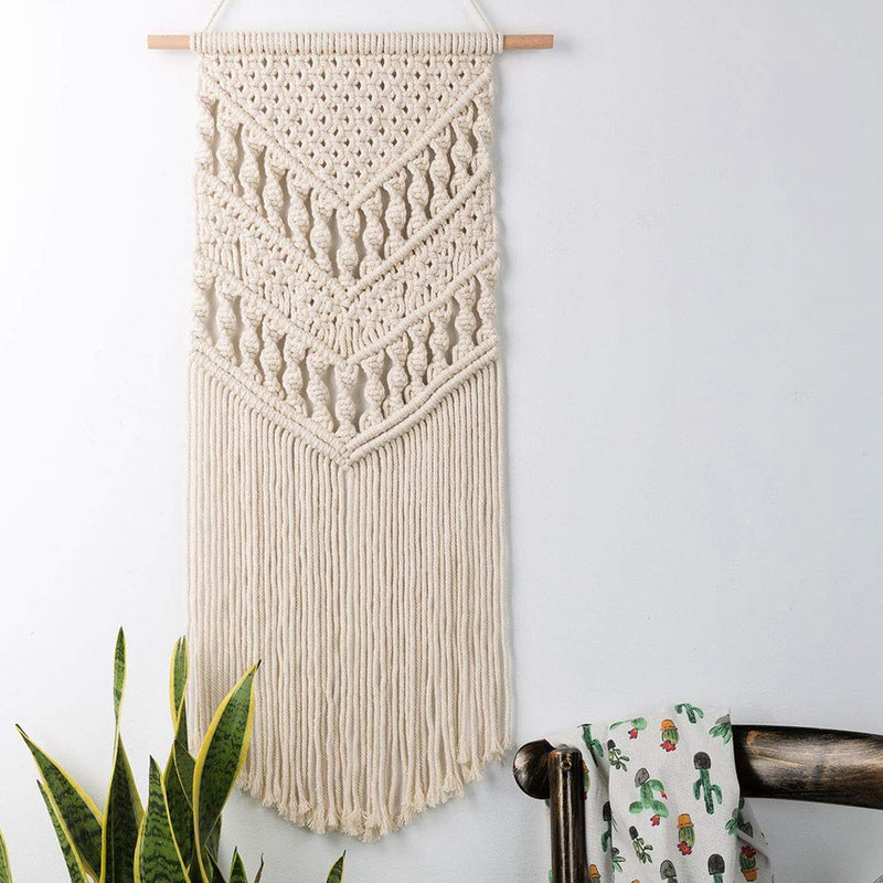 Image shows Piha wall hanging. It is a macrame weaving with a piece of wood across the top and  the macrame in a long oblong shape hanging from the wood. It is heavily textured with a triangle shape and the top, and twists of macrame. The bottom has a long fringe.