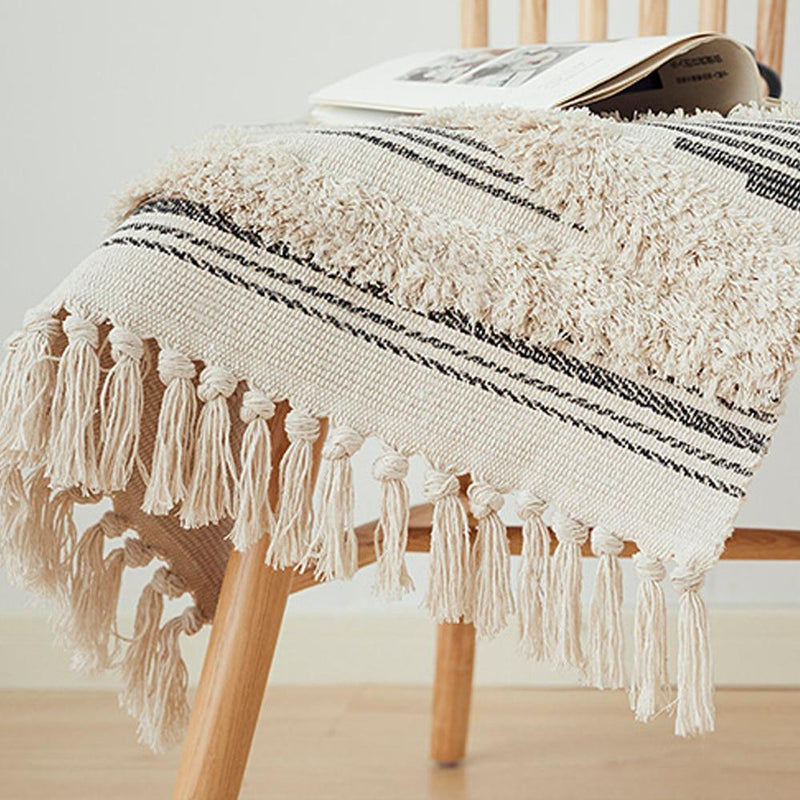 Image shows a rug draped over a chair. It has tassels on the ends and a heavy tuffed pattern in large diamond shapes. It is a natural unbleached colour with dark stripes.