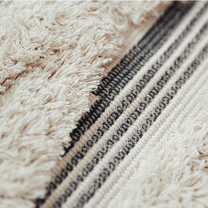Image shows close up shot of the texture on a rug. It has tassels on the ends and a heavy tuffed pattern in large diamond shapes. It is a natural unbleached colour with dark stripes.