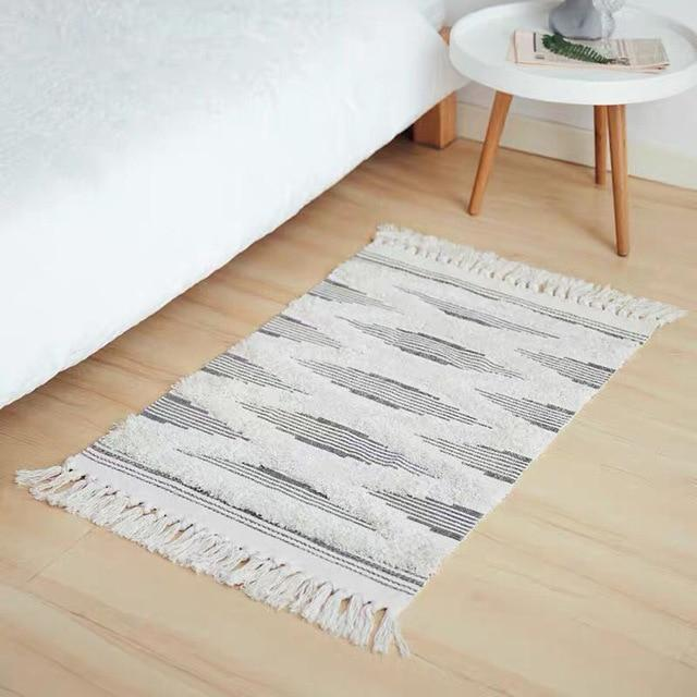 Image shows a rug on the floor by a bed and bedside table. It has tassels on the ends and a heavy tuffed pattern in large diamond shapes. It is a natural unbleached colour with dark stripes.
