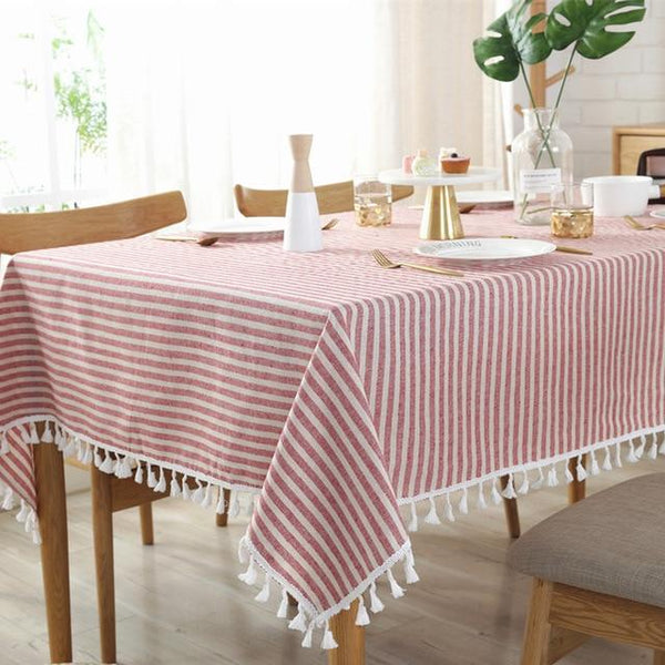 Red strip linen table cloth is shown on a wood dining table with chairs and the table set with plates. The table cloth is a woven fabric with cream tassels along the edge and is striped red and white.
