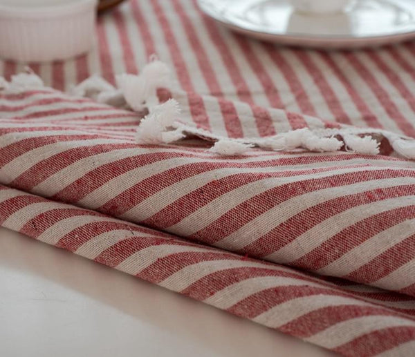 A close up ohoto of the red stripe linen table cloth. It shows small cream tassels along the edge and red and white stripes on the tablecloth