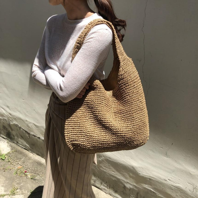 A woman wears the slouchy tote in coffee on her shoulder. It is a simple shoulder tote shape and both bag and shoulder straps are woven in straw. It has a slouchy unstructured shape and is plain and unembellished.