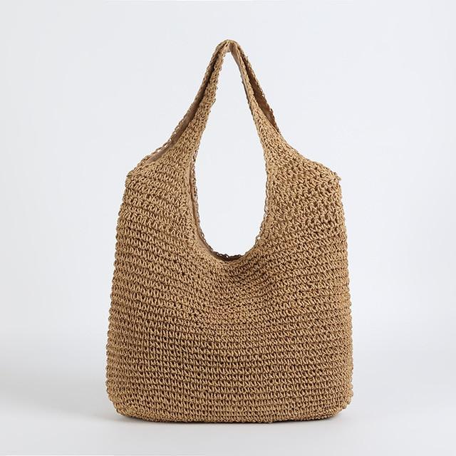 Image shows the slouchy tote in coffee. It has a simple shoulder tote shape and both bag and shoulder straps are woven in straw. It has a slouchy unstructured shape and is plain and unembellished.